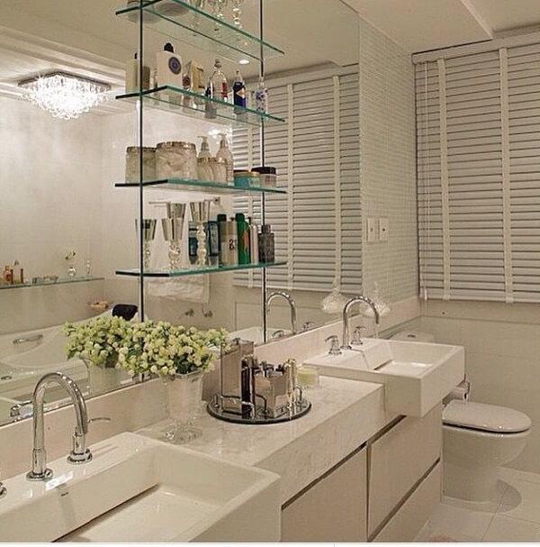 Bandeja espelhada e vaso de flor usadas como enfeites para banheiro