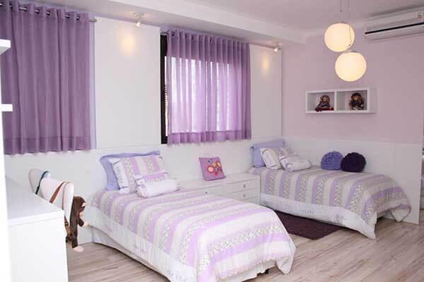 Cor lilás em quarto de criança com duas camas