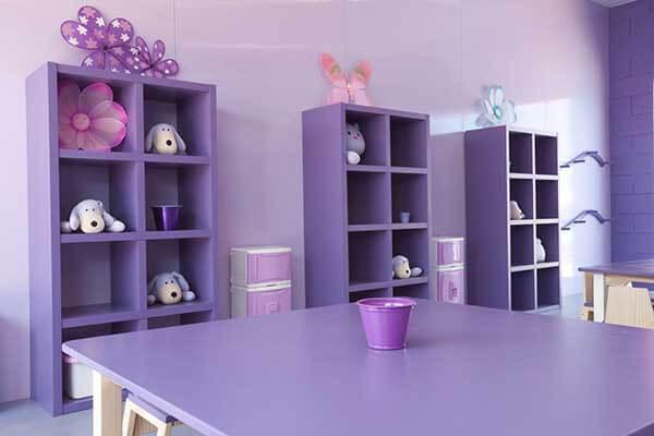 Cor lilás em sala de creche com nichos e mesas da mesma cor