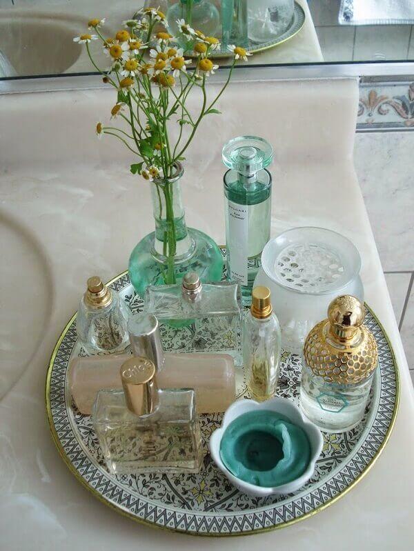 Vidros e frascos vintage utilizados como enfeites para pia de banheiro