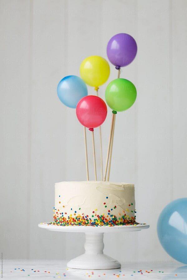 bolo de festa de aniversário simples decorado com granulado colorido e balões no topo Foto SistaCafe
