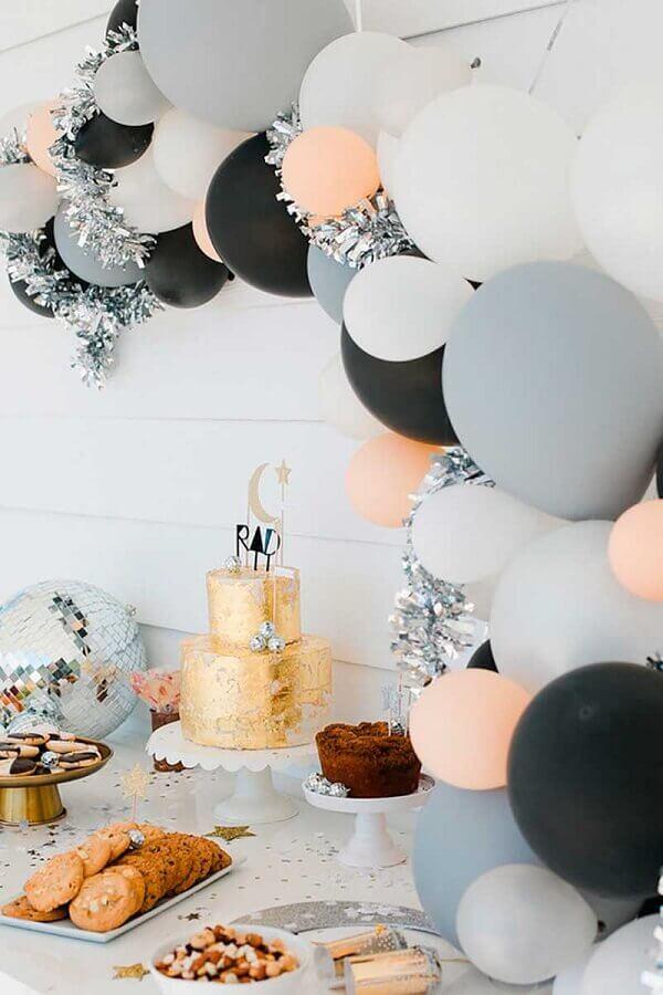 decoração de festa de aniversário com arranjos de balões e bolo dourado  Foto Air Freshener