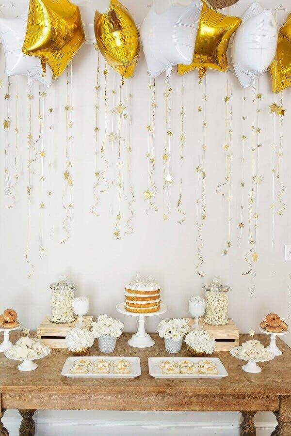 decoração para festa de aniversário branca e dourada com balões em formato de estrela e mesa de madeira  Foto Suzanne Carey Photography