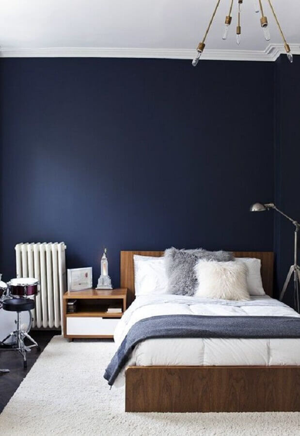 decoração para quarto azul marinho com luminária moderna e cama de madeira Foto Decofinder