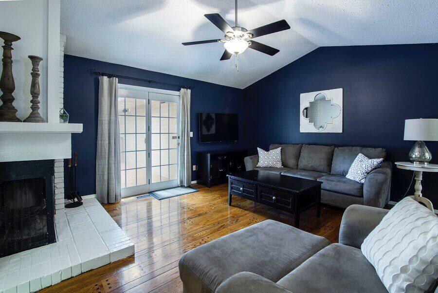 decoração sala de estar azul com sofá cinza e piso de madeira Foto Pexels