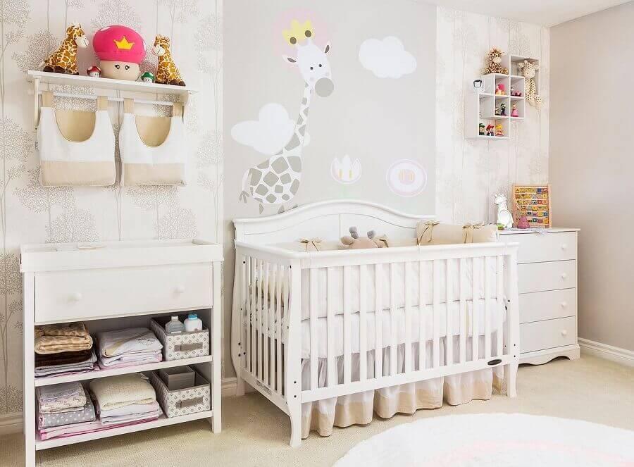 prateleira com varão para quarto de bebê todo branco com adesivo de girafa na parede Foto Andrea Bento