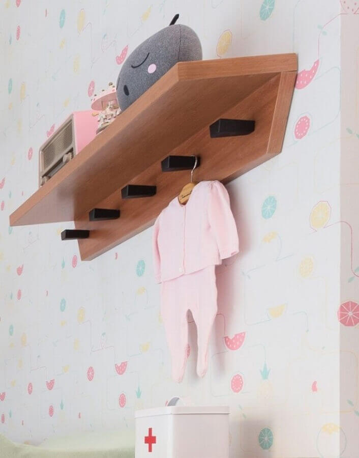 prateleira de madeira para quarto de bebê com ganchos decorado com roupinha de bebê Foto Blog da Giovanna