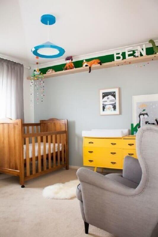 prateleira de madeira para quarto de bebê decorado com cômoda amarela e poltrona cinza Foto Viajando no Apê
