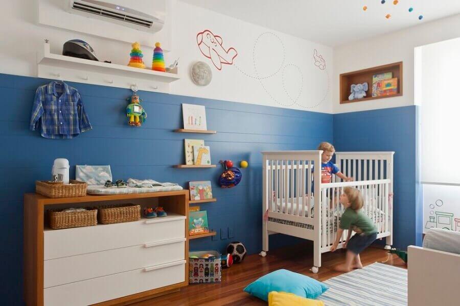 quarto de bebê azul decorado com cômoda de madeira e tapete listrado Foto Natoca Design