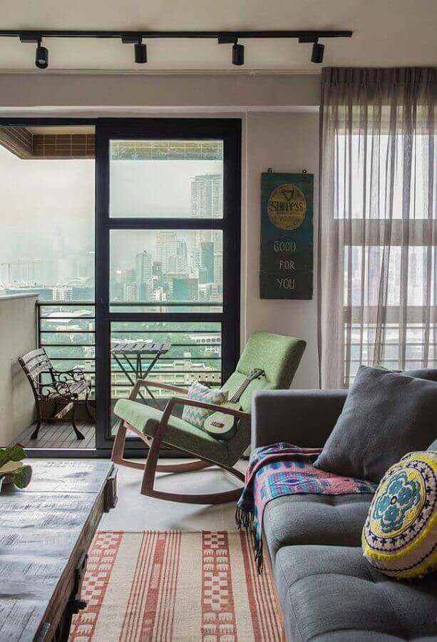 sala decorada com cadeira de balanço de madeira e estofado verde Foto Neu dekoration stile