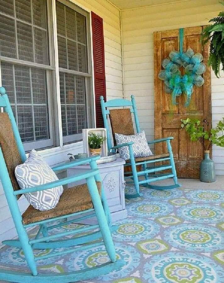 varanda simples decorada com cadeira de balanço de madeira pintada de azul Foto QuitDecor