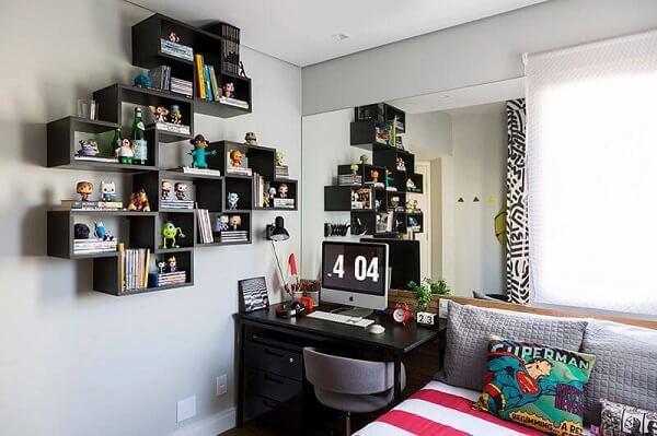 Com efeito decorativo, a estante preta guarda livros e exibe a coleção de bonecos