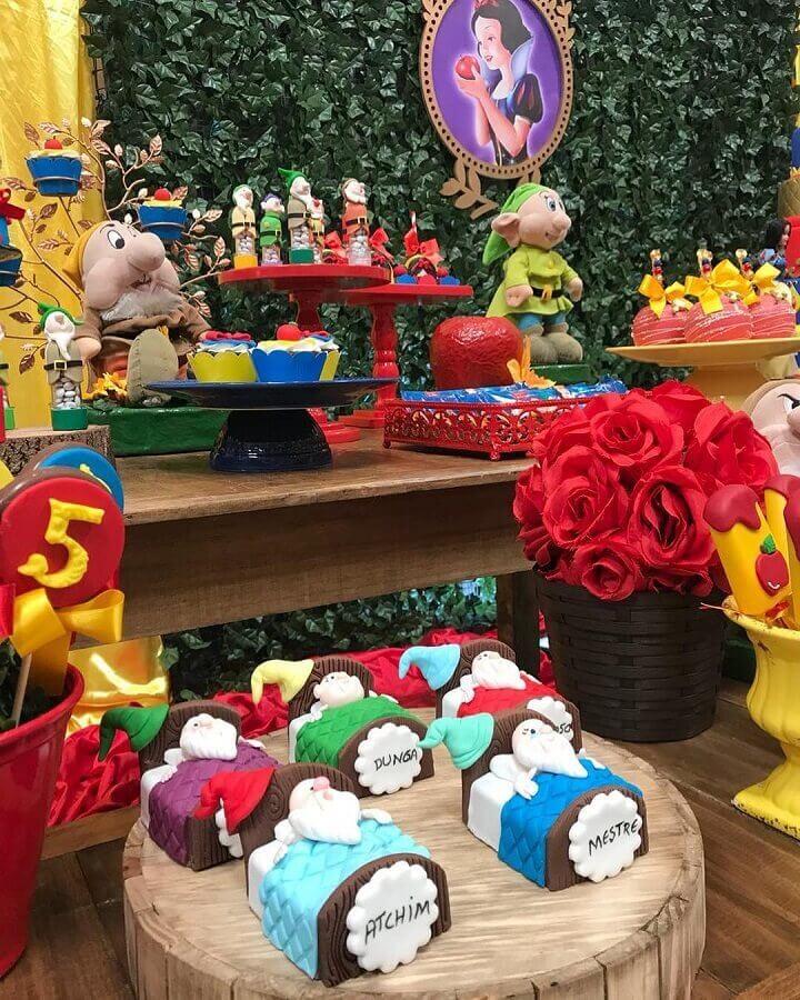 festa branca de neve decorada com painel de folhagem e vários bonequinhos sobre a mesa Foto Simone Lopes