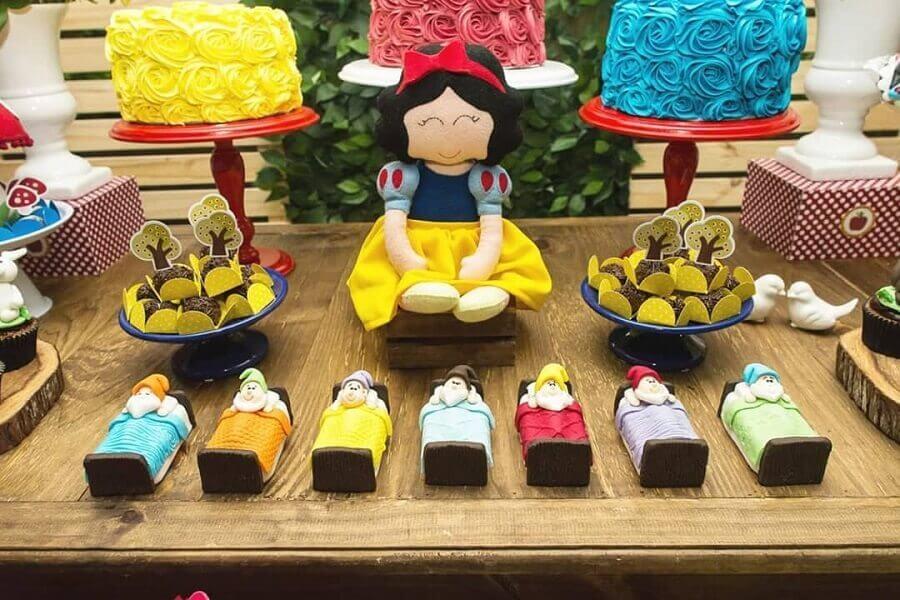 mesa para festa da branca de neve com personagens dos sete anões e três bolos Foto Arca da Chapéu