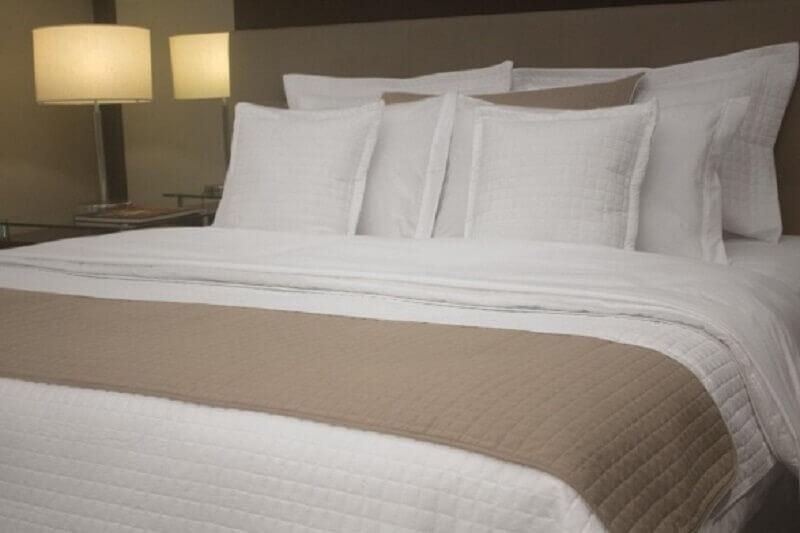 quarto de hotel com roupa de cama branca e bege