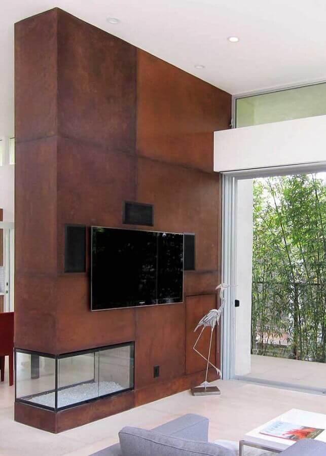 sala de TV decorada com lareira de canto e porcelanato aço corten  Foto Pinosy