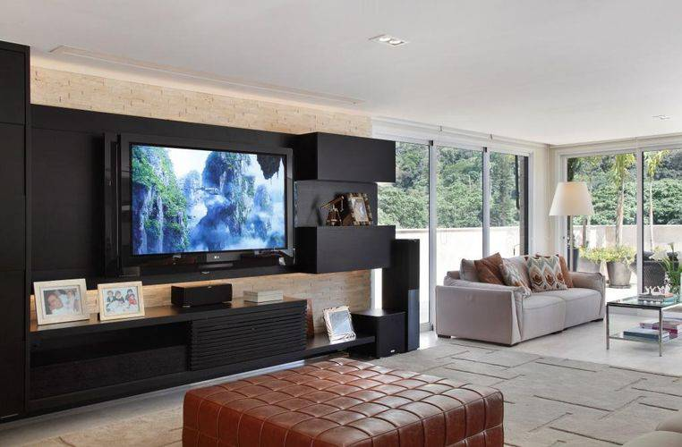 O rack com painel de TV na cor preta é o destaque dessa sala decorada. Projeto de Vivian Coser