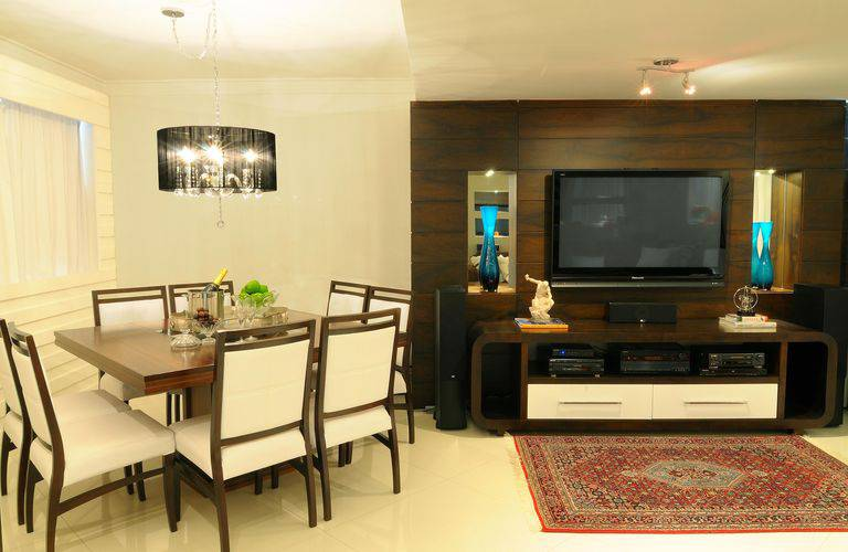 O painel paraTV feito de madeira pode ocupar toda a parede, como nessa decoração que conta até mesmo com home theater