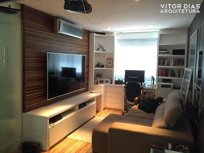O painel de TV feito em madeira deixou o ambiente mais aconchegante e serviu como suporte para TV e para o ar condicionado. Projeto de Vitor Dias