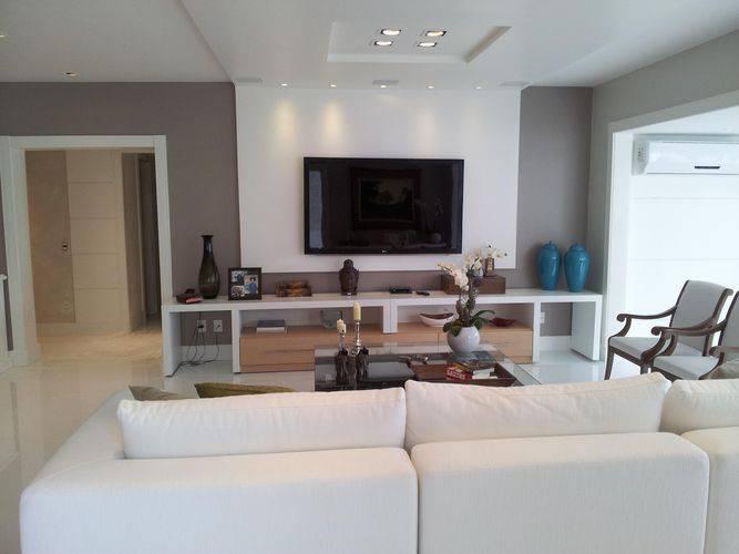 O painel para TV branco e integrado ao teto dá a sensação que o ambiente é maior. Projeto de Lucio Nocito