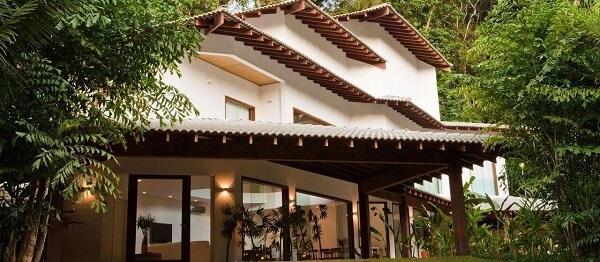 Casa com teto colonial e tipos de telhas acinzentadas