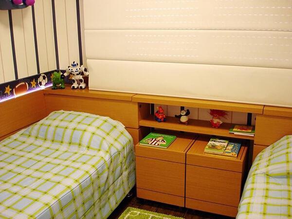 Quarto infantil planejado em apartamento com baú de brinquedos de madeira
