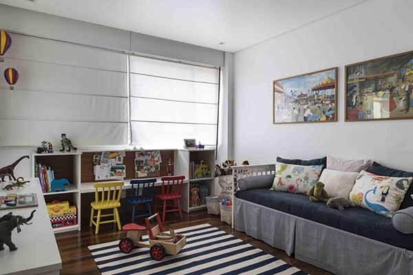 Quarto infantil planejado com cadeiras coloridas e tapete listrado