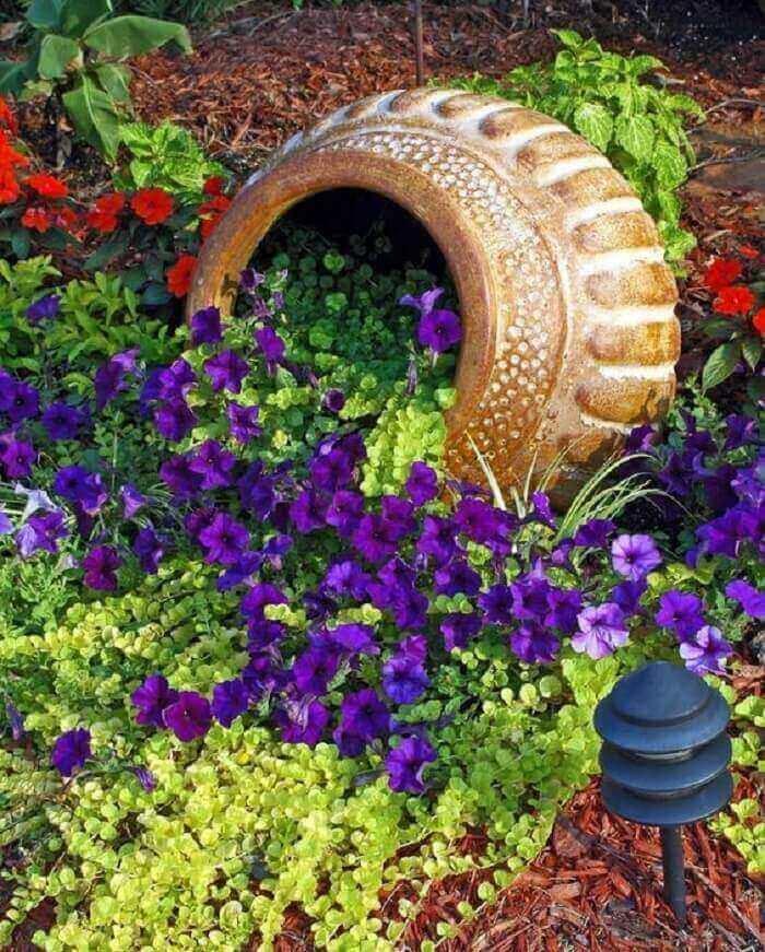 Vaso inclinado e flores de petúnia esparramadas no solo