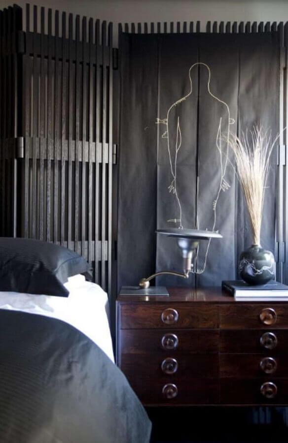 comoda retro de madeira em quarto de casal decorado todo preto