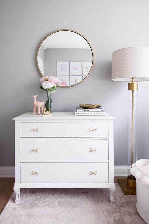 decoração com cômoda branca com puxador em formato de laço e espelho redondo Foto Decorpad