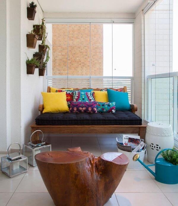 sofá de madeira com almofadas soltas coloridas