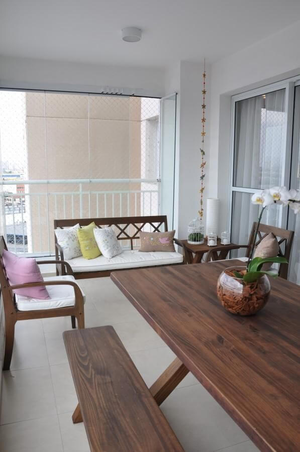 varanda com sofá de madeira e mesa