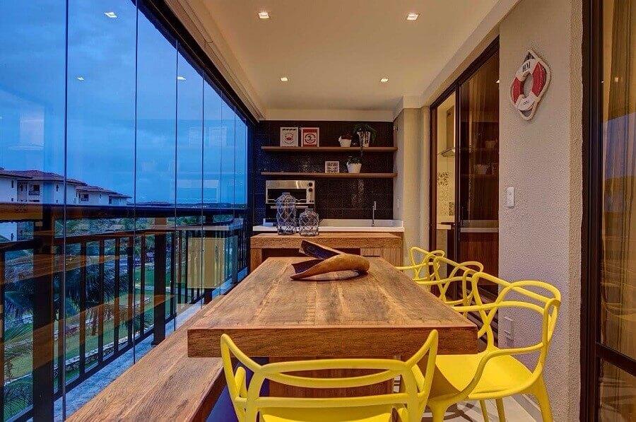 varanda gourmet decorada com cortina de vidro  e cadeiras amarelas