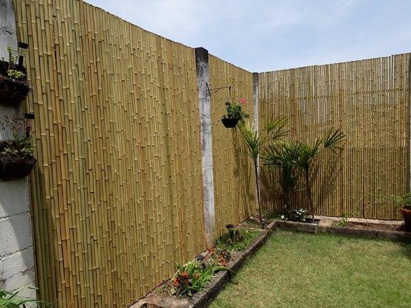Jardim externo delimitado com cerca de bambu