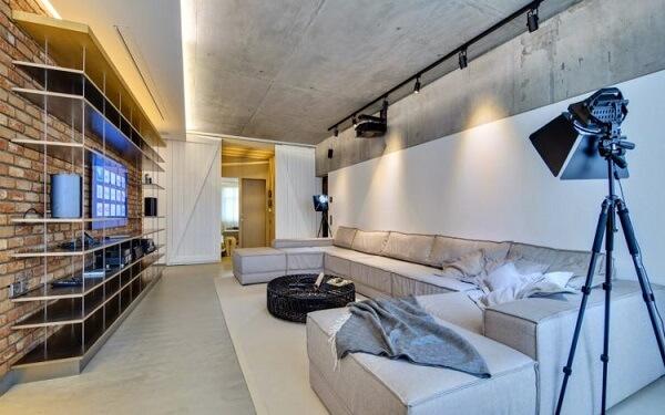 Ambiente descontraído com parede de cimento queimado e Spot de trilho
