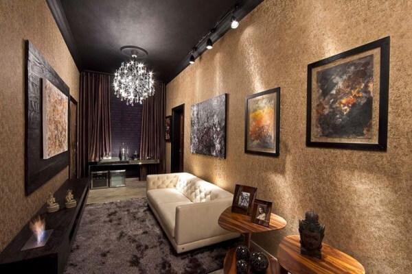 Ambiente elegante decorado com sofá em capitonê e luz Spot trilho