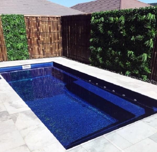 O jardim vertical e a cerca encantam a decoração da piscina