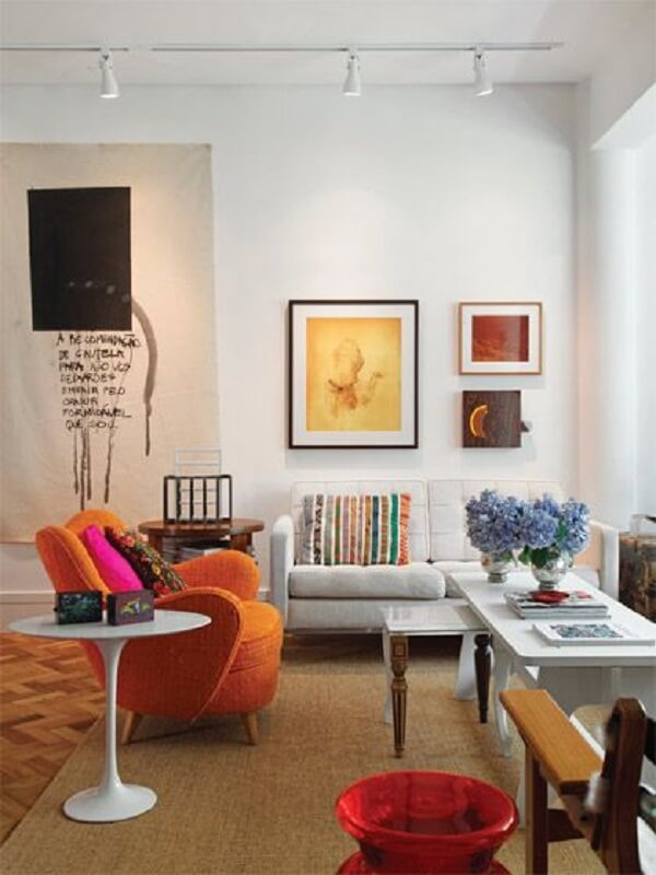 Spot de luz trilho em tom branco complementa a decoração da sala de estar