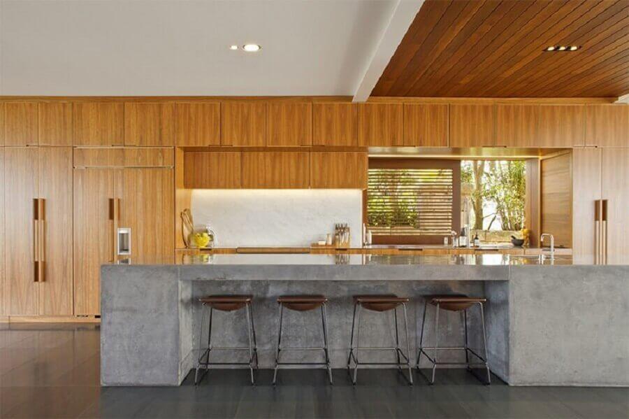 cozinha ampla com bancada de concreto e armários de madeira Foto Limaonagua