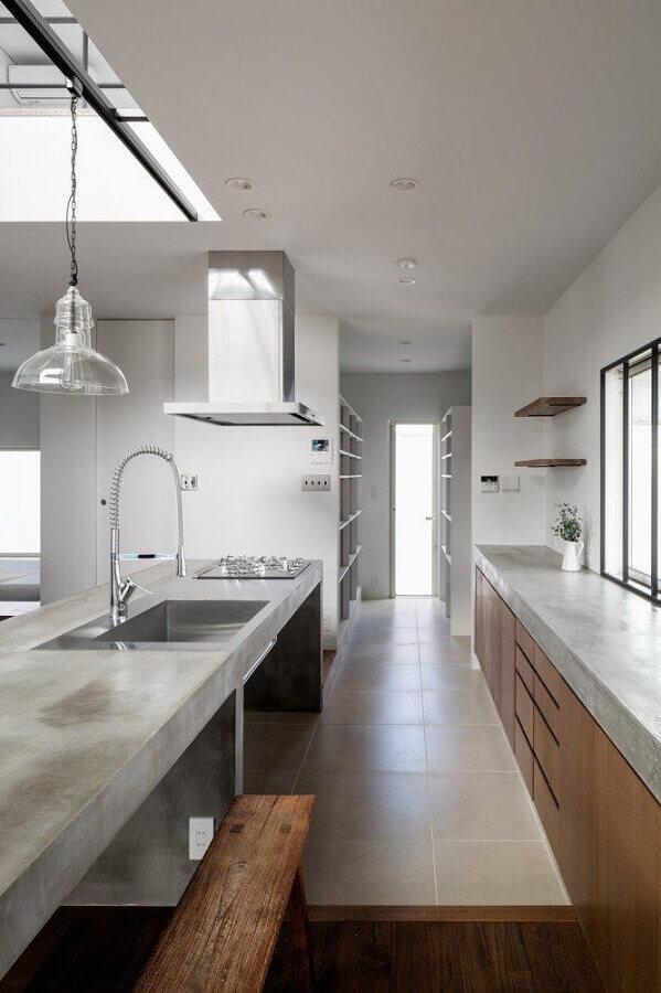 cozinha com bancada de concreto com pia e cooktop e armários de madeira Foto ArchDaily