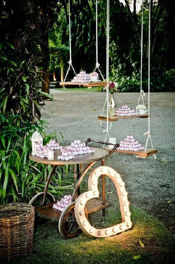 decoração de casamento no campo com doces apoiado em balanças  Foto Weddbook