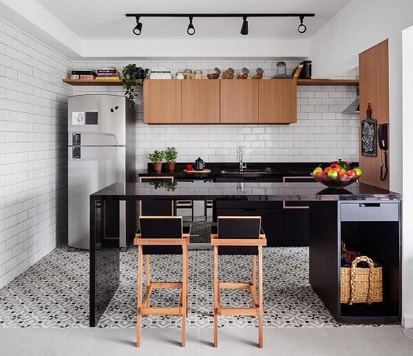 Cozinha com bancada preta e Spot de trilho preto