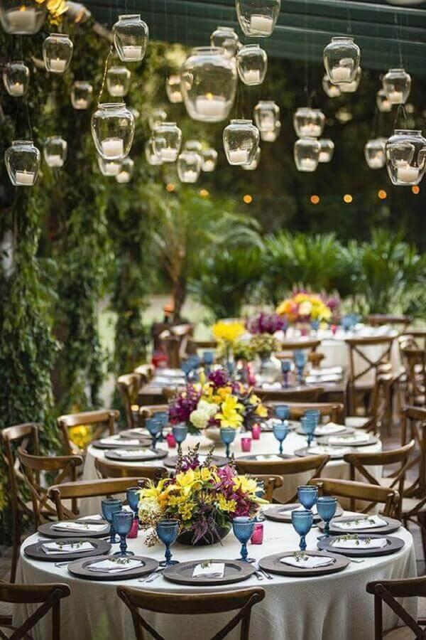 festa de casamento no campo decorada com velas suspensas e arranjo de flores coloridas  Foto Luxury Wedding