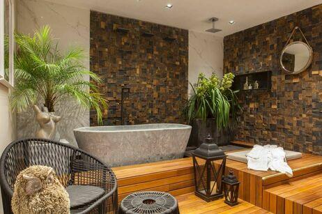 parede de pedra - banheira de pedra cinza e cadeira de fibra escura