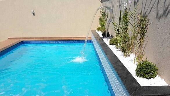 Piscina de vinil com cascata em canto com pedrinhas brancas