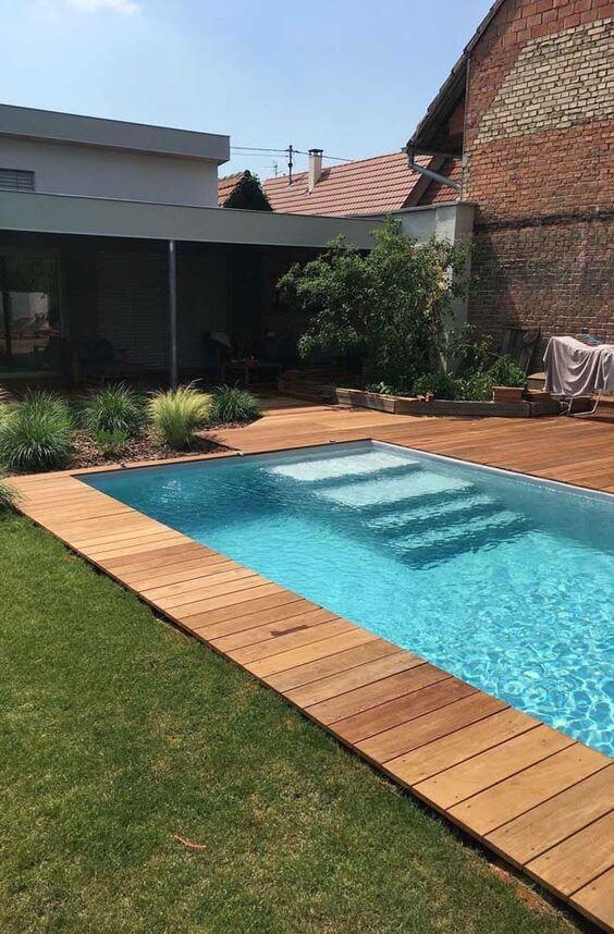 Borda de piscina alvenaria com madeira e gramado