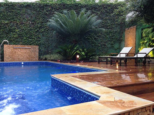Borda de piscina com pedra e madeira