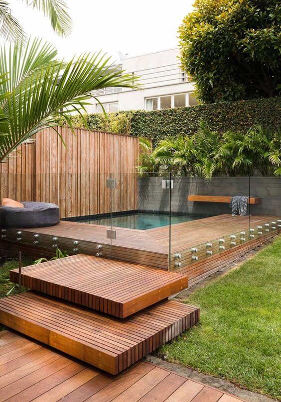 Borda de piscina com vidro de madeira na área da piscina