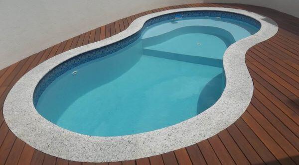 Borda de piscina com granito e madeira