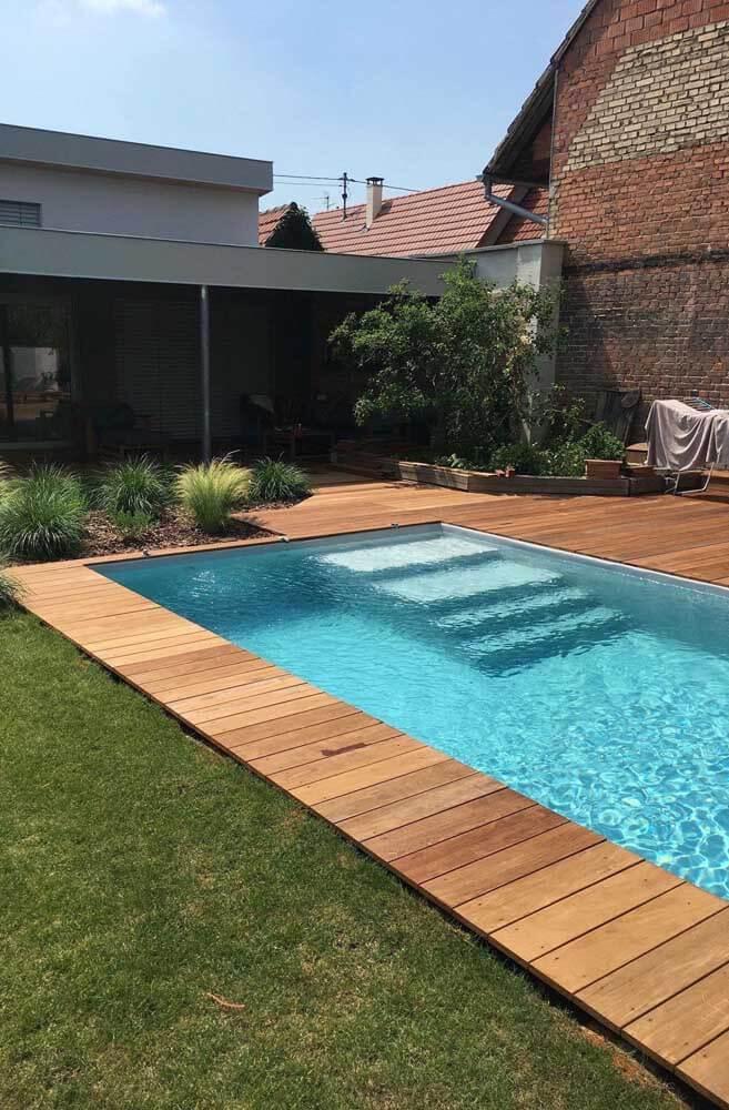 Borda de piscina de madeira com grama verde